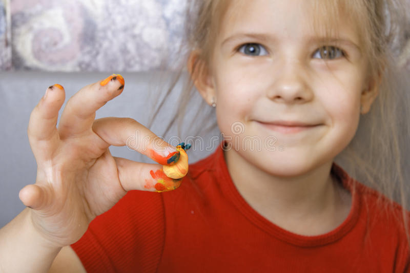 Girl shows a homemade painted crafts. Focus on the hand stock photos