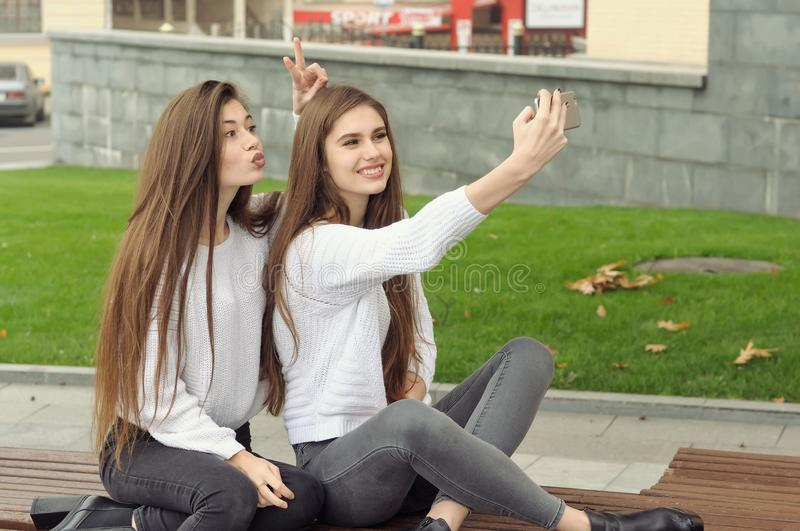 Girl shows the horns to the girlfriend while they make a selfie. Photo. They both have long brown hair that is long to the waist and they are dressed in royalty free stock photos