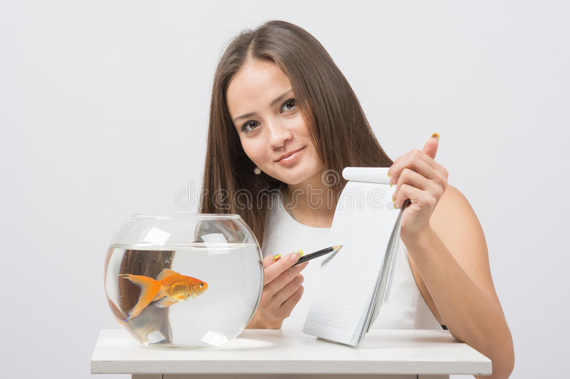 Girl shows a pen in a notebook record gold fish in the aquarium. A young girl sits next to a round aquarium in which swimming goldfish stock photography