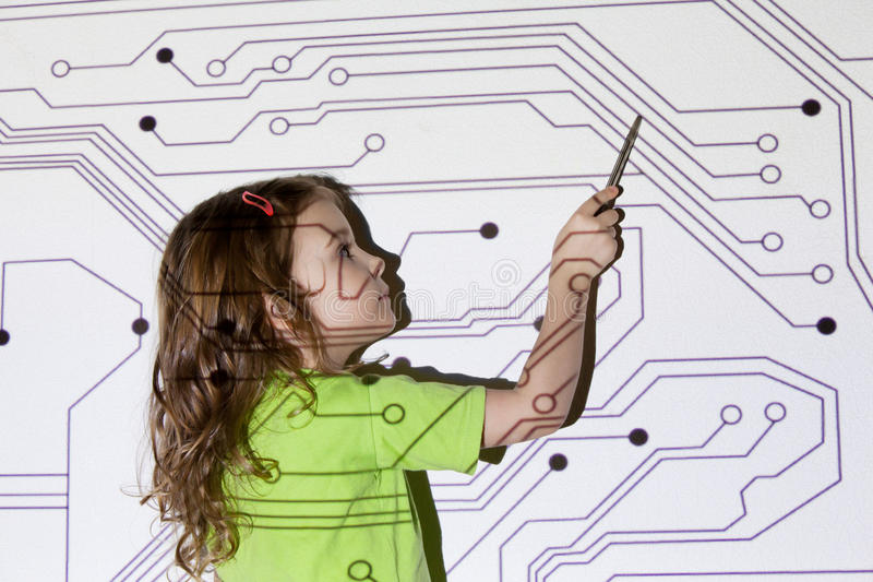 Girl shows pointer on electric scheme. Pretty little girl shows pointer on electric scheme throw projector on wall royalty free stock photography