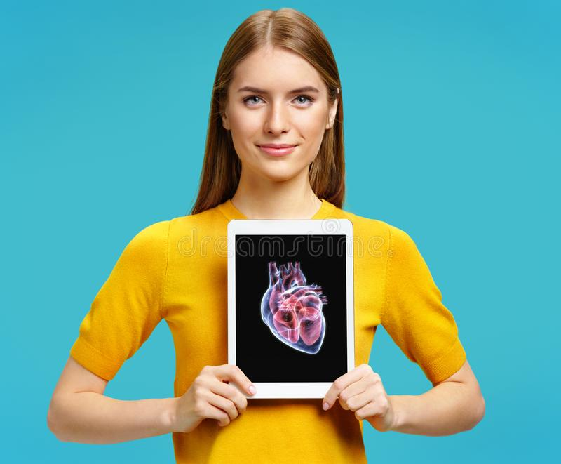 Girl shows the x-ray image of the heart. Photo of young girl with tablet in her hands royalty free stock image