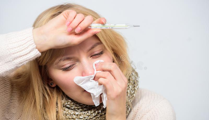 Girl sick hold thermometer and tissue. Measure temperature. Break fever remedies. Seasonal flu concept. Woman feels stock image