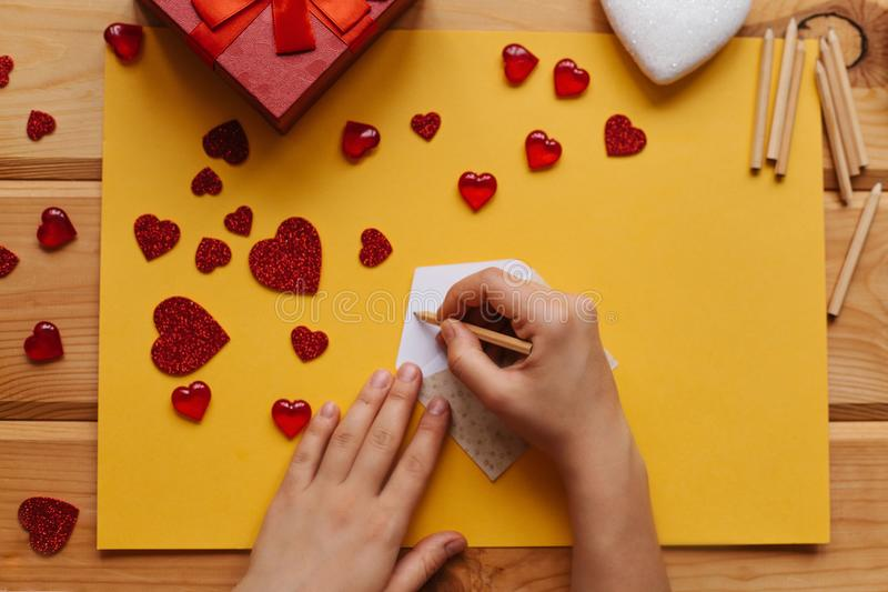 The girl signs an envelope with congratulations on the holiday to send it, beside on the wooden surface lie gifts stock photo
