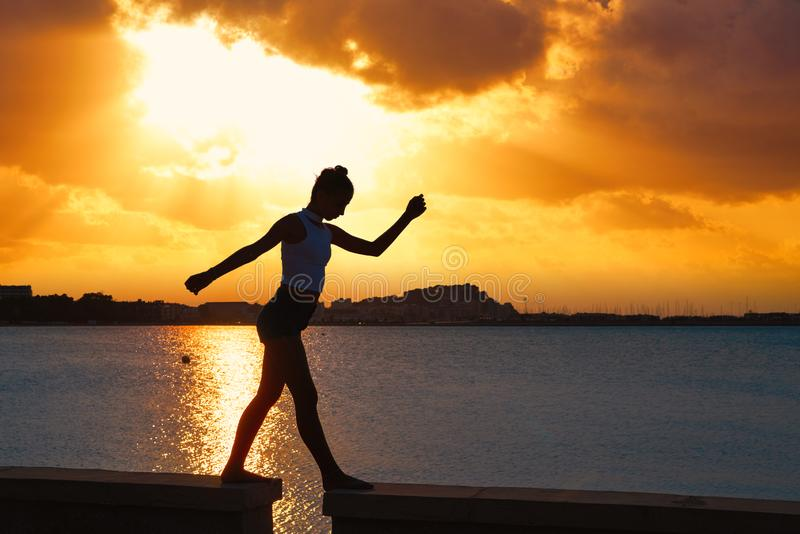 Girl silhouette at beach sunset gymnastics stock image