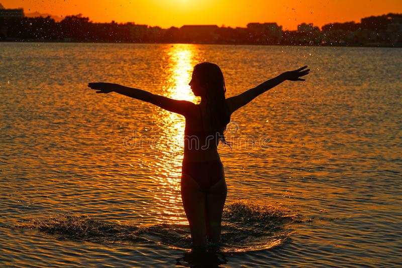 Girl silhouette at beach sunset open arms stock photography