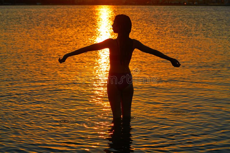 Girl silhouette at beach sunset open arms stock images