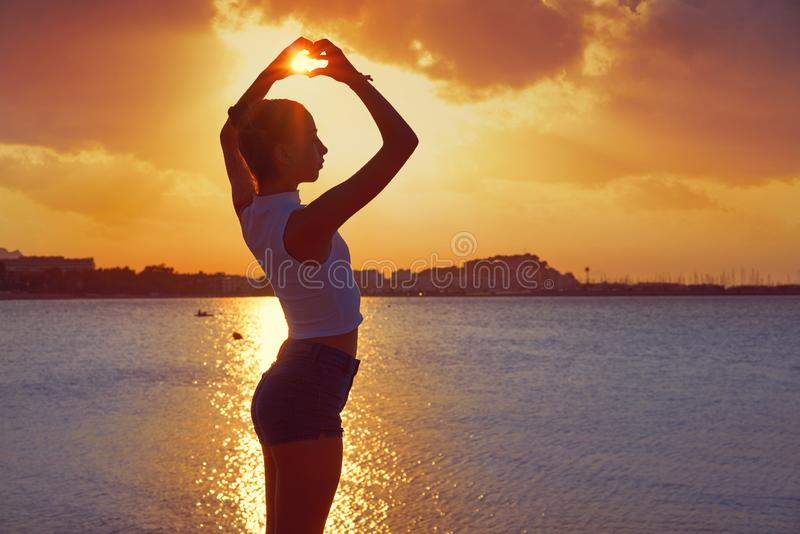 Girl silhouette at beach sunset heart shape stock photography