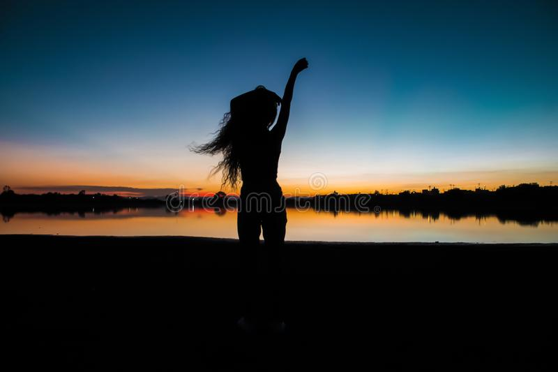 Girl silhouette at twilight with lake background stock photo