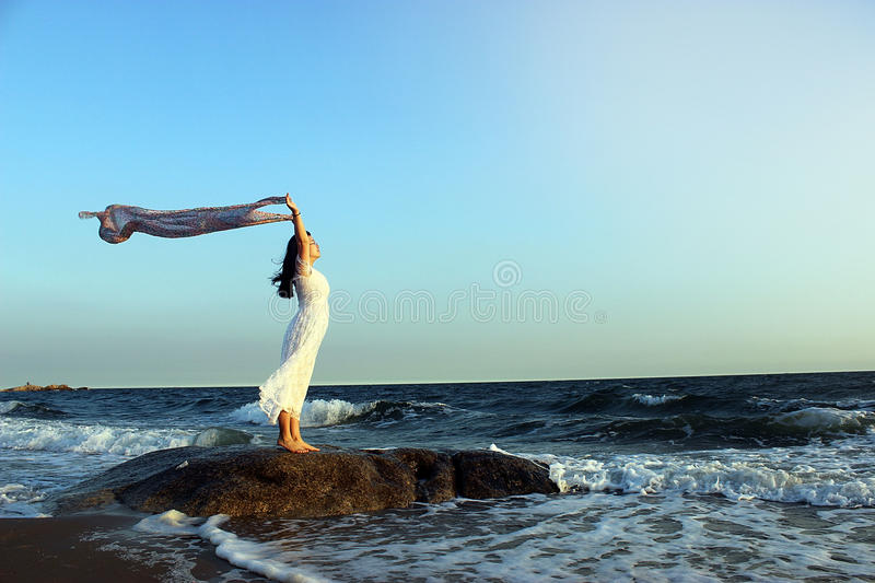 A girl with a silk scarf look into the sea horizon royalty free stock image
