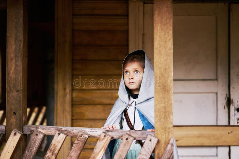 Little girl silver cloak hood looking sky old abandoned house building fairy tale story blue eyes riding. Girl silver cloak hood looking sky old abandoned house stock photos