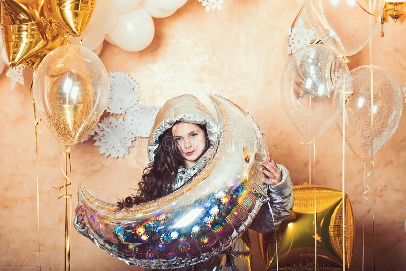 Girl with silver crescent moon balloon, ramadan. Small child in winter jacket with party balloons. Party decor and stock image
