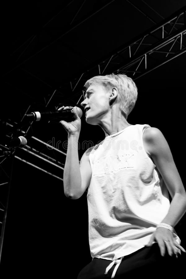 Girl singer with short blonde hair sings at a rock concert. Black and white photo stock photos