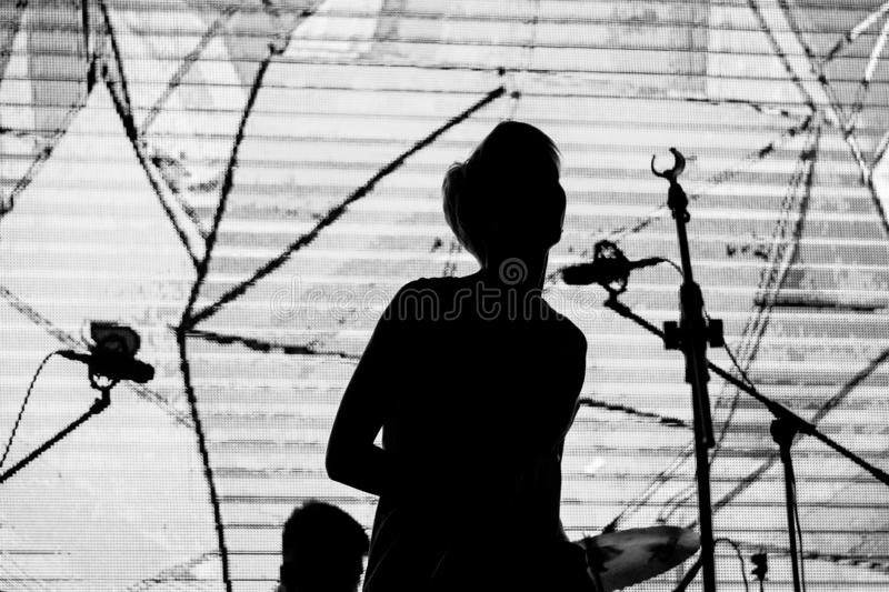 Girl singer with short blonde hair sings at a rock concert. Black and white photo royalty free stock photos