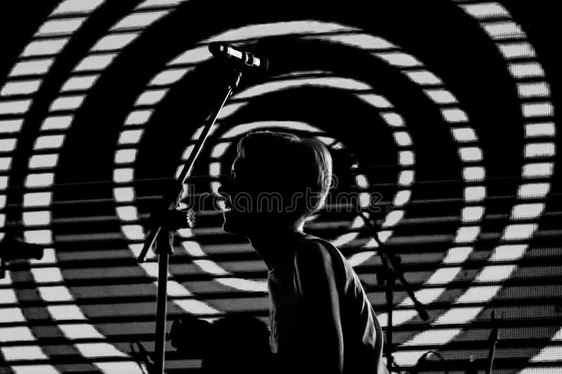 Girl singer with short blonde hair sings at a rock concert. Black and white photo royalty free stock photography