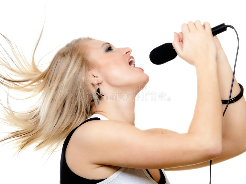 Girl singer singing to microphone isolated on white. Emotional blonde girl singer performer singing to microphone isolated on white. young pretty rockstar royalty free stock images