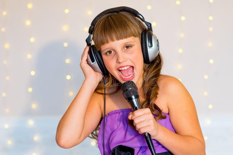 Girl singing on karaoke. Girl with headphones singing on karaoke solo on background of lights royalty free stock image