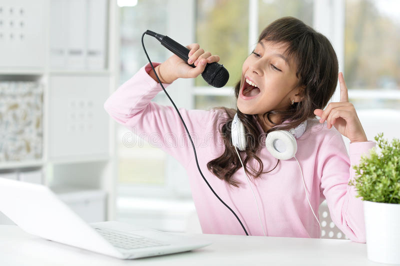 Girl singing songs. Portrait of a girl singing songs, using laptop stock images