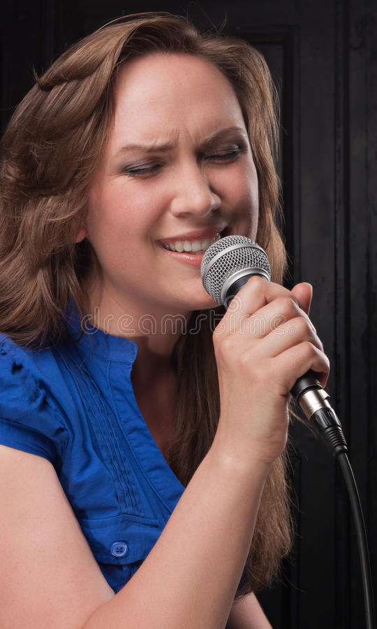 Girl singing to the microphone in a studio. Studio shooting on a dark gray background royalty free stock images