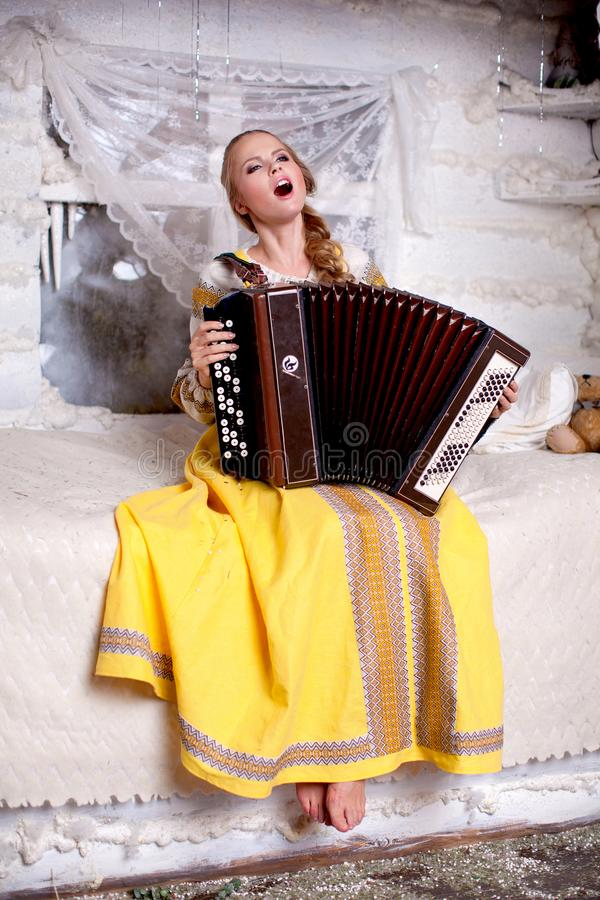 The girl sings and plays the accordion. A beautiful blonde girl with a long braid and a yellow sundress sings and plays the accordion stock image