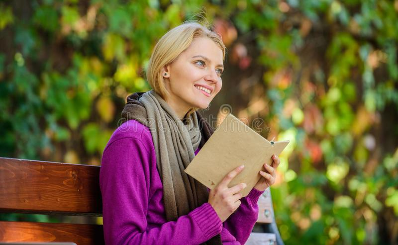 Girl sit bench relaxing with book fall nature background. Book list for autumn season. Intellectual hobby. Lady bookworm. Read book outdoors fall day. Woman royalty free stock photography