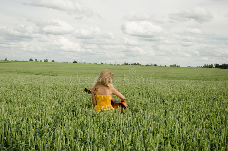 Girl sit in field of rye plays guitar stock photos
