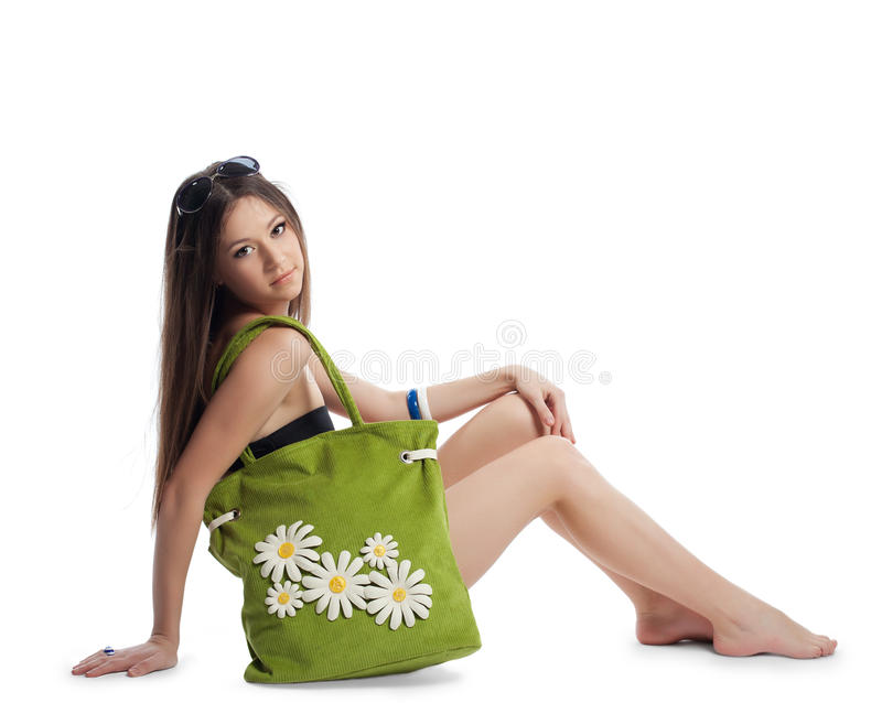 Girl sit with green beach bag isolated on white stock images