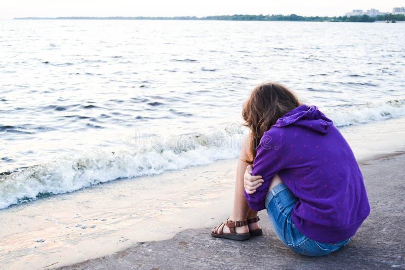 Girl siting at riverside stock photo