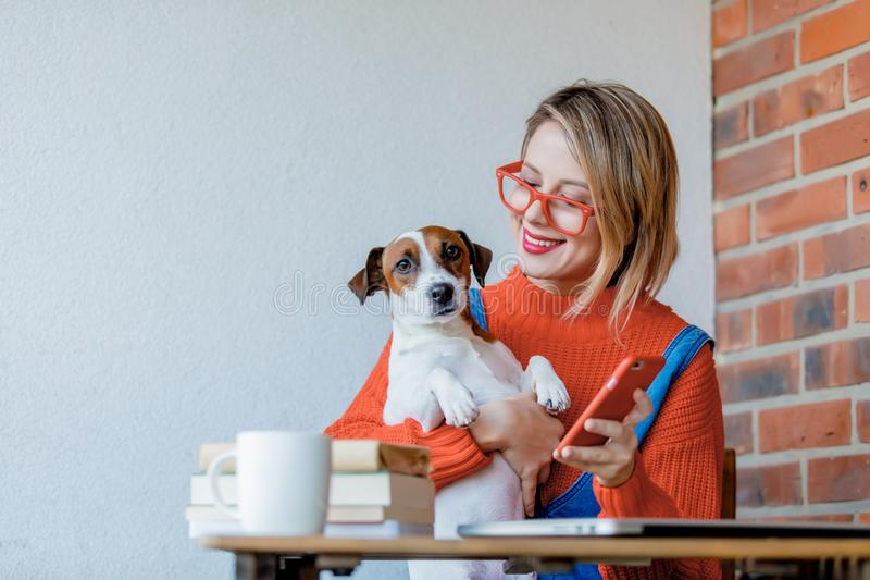Girl sititng at table with computer and dog stock images