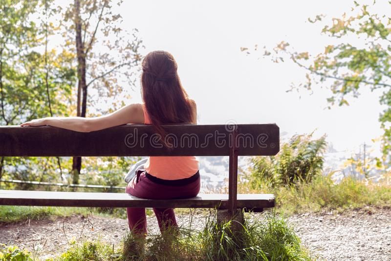 A girl sits on a bench in the forest, her back to the camera stock photos