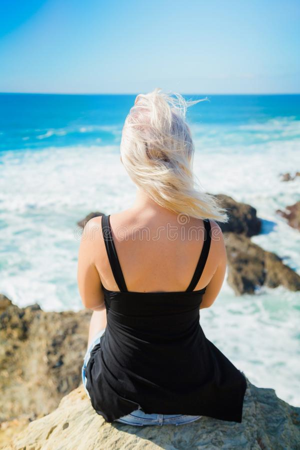 Girl sits on a cliff above the ocean stock images