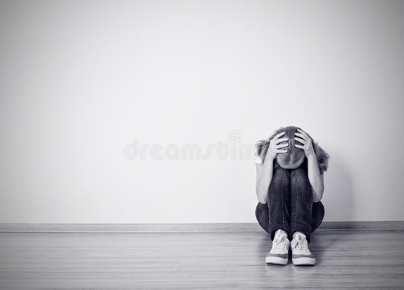 Girl sits in a depression on the floor near the wall stock image