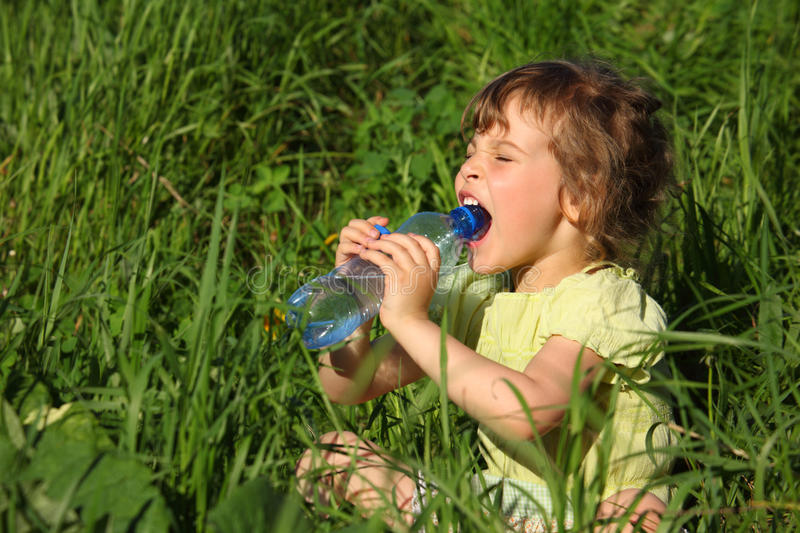 Girl sits and drinks water from bottle stock images