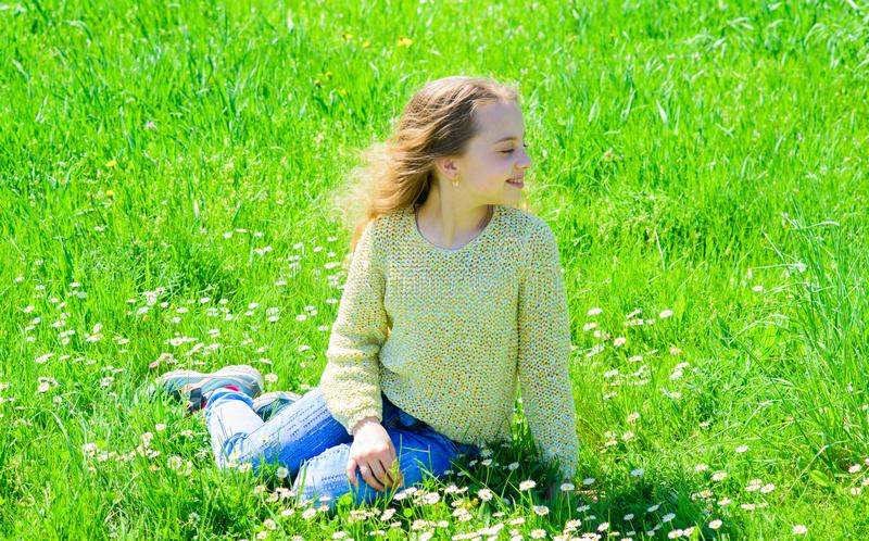 Girl sits on grass at grassplot, green background. Child enjoy spring sunny weather while sitting at meadow. Springtime stock photo