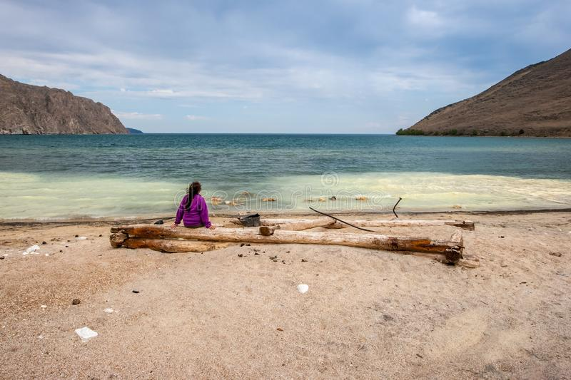 The girl sits with her back on old logs on the sandy shore of the bay of Lake Baikal and looks at the water. Water of different colors with small waves. There royalty free stock photo