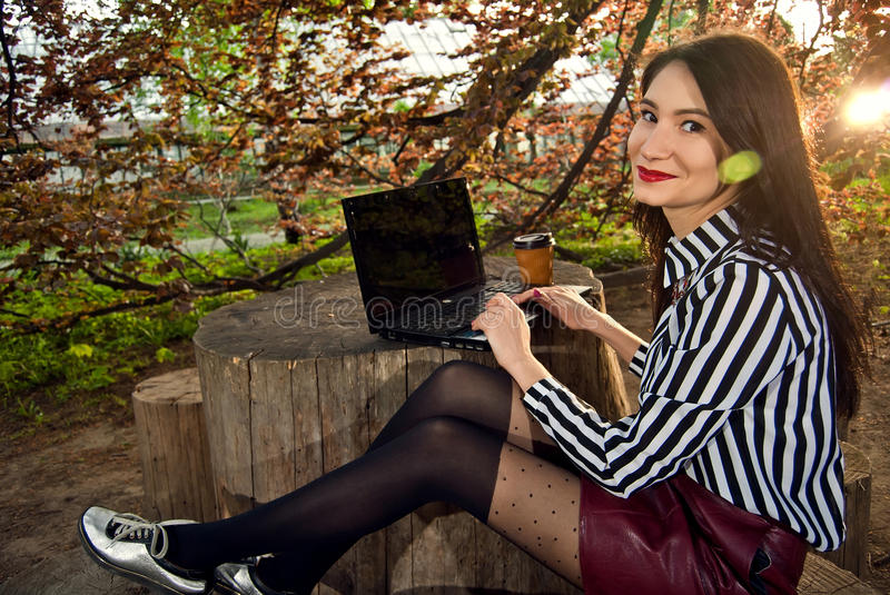 Girl sits with a laptop in the nature stock photo