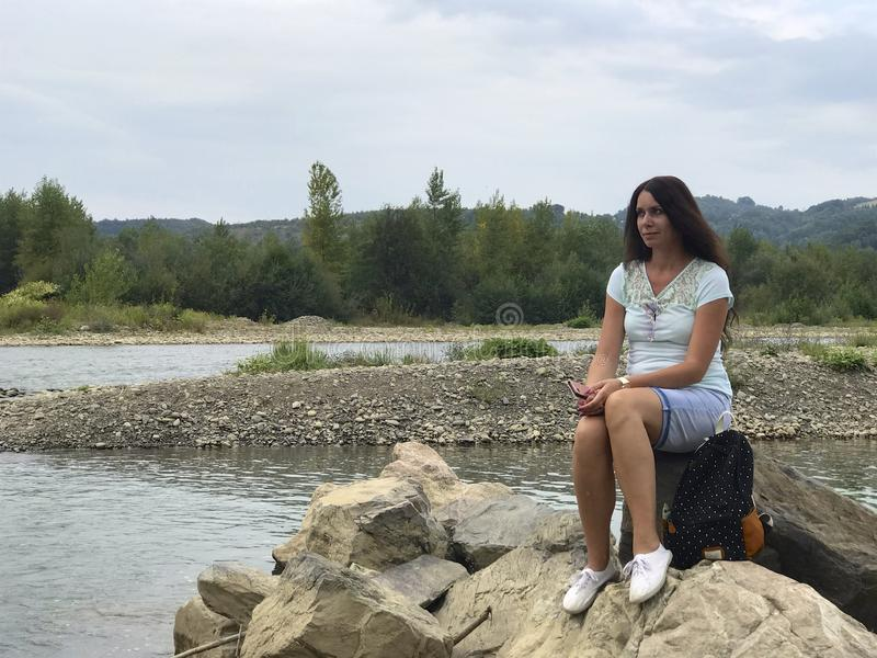 A girl sits on a large boulder near a mountain river. backpack. She is looking at the water stream.  stock images