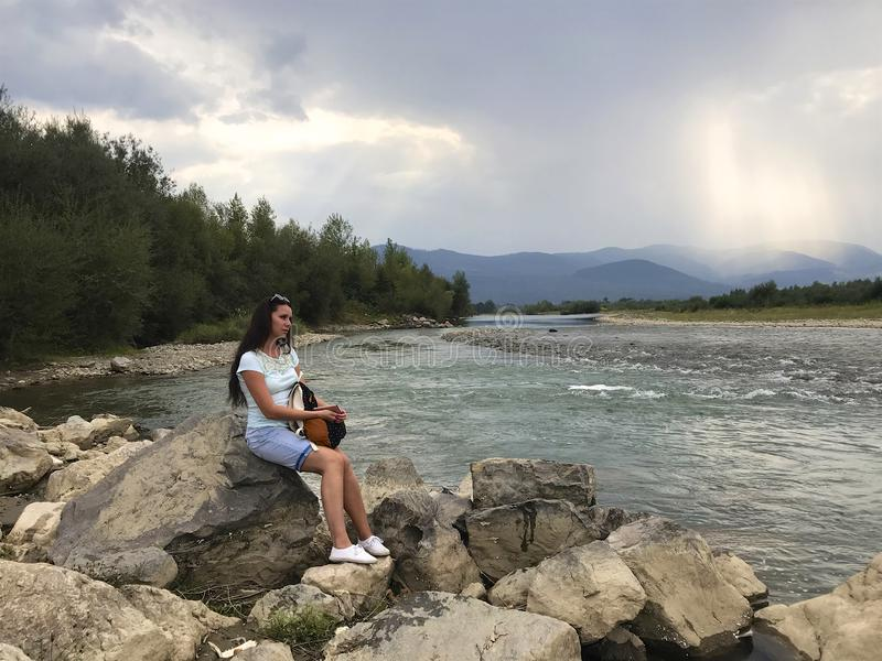 A girl sits on a large boulder near a mountain river. Holds a tourist backpack on his lap. She is looking at the water stream.  royalty free stock photos