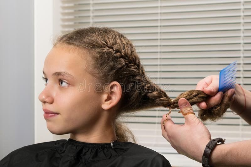 The girl sits at the master on hairdresses, does a stacking stock images
