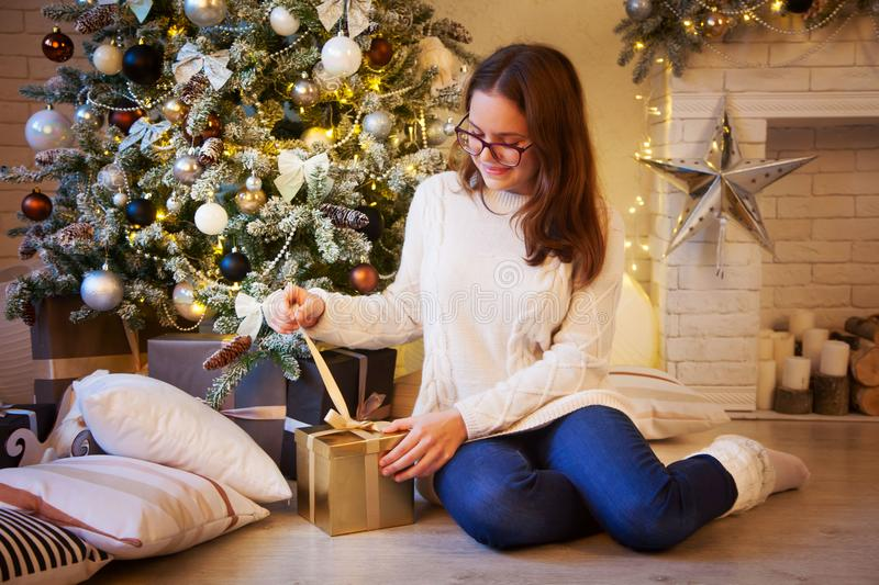 The girl sits near the Christmas tree and opens the golden gifts. Christmas fireplace and a lot of gifts and surprises stock photo