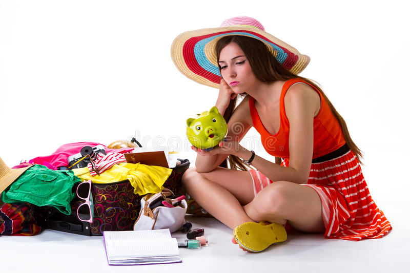 Girl sits near open suitcase. Woman with green money box. She dreams of better days. Not enough money for vacation stock photo