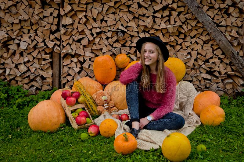 The girl sits next near for pumpkins. Thanksgiving, Halloween royalty free stock photos