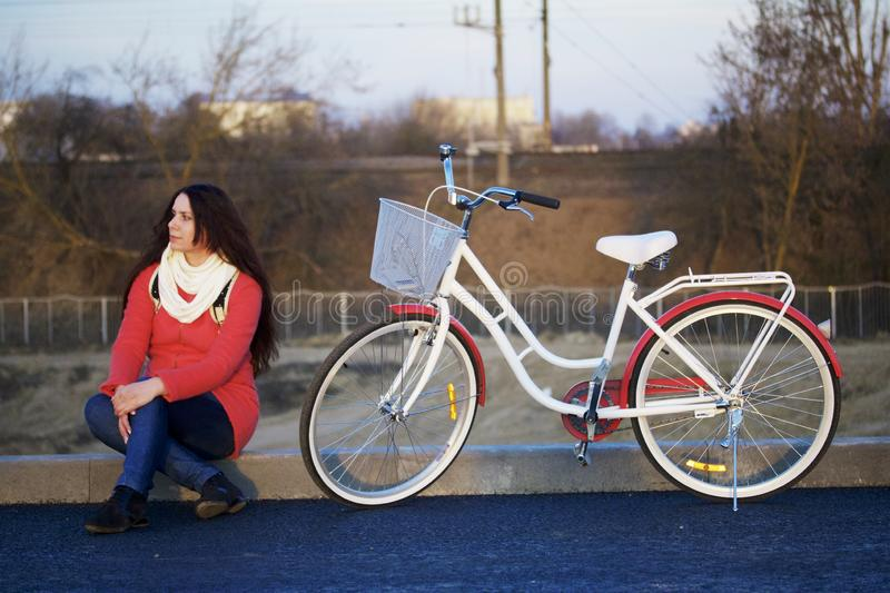 The girl sits next to a parked bike. Rest on the spring cycle.  royalty free stock photography