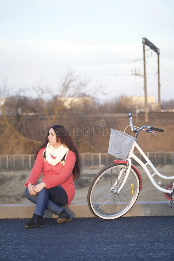 The girl sits next to a parked bike. Rest on the spring cycle royalty free stock images