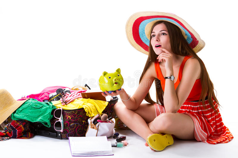 Girl sits beside overfilled suitcase. royalty free stock photography