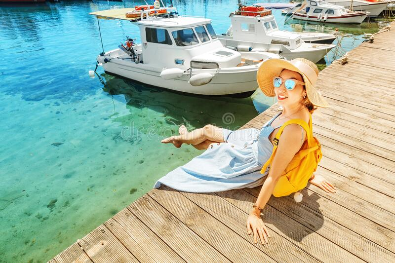 Girl sits on the pier near the parked boats on the Mediterranean coast. Vacation and travel concept. The girl sits on the pier near the parked boats on the stock photography