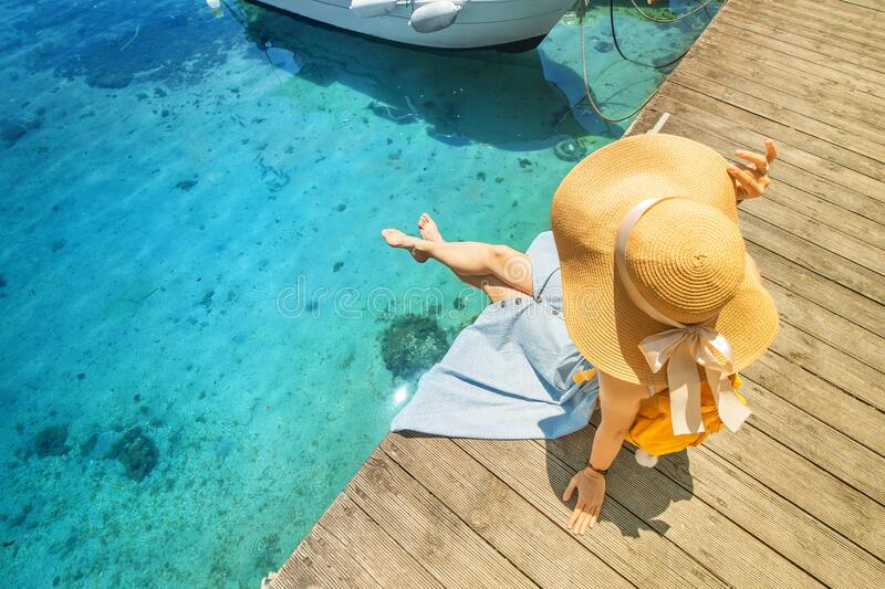 Girl sits on the pier near the parked boats on the Mediterranean coast. Vacation and travel concept. The girl sits on the pier near the parked boats on the stock images