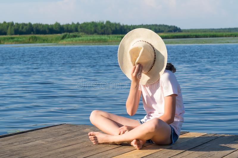Girl sits on a pier by the river, covers her face with a hat against the blue sky stock photo