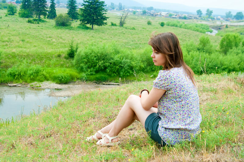 Download The Girl Sits On The Rock Royalty Free Stock Photos - Image: 29106788
