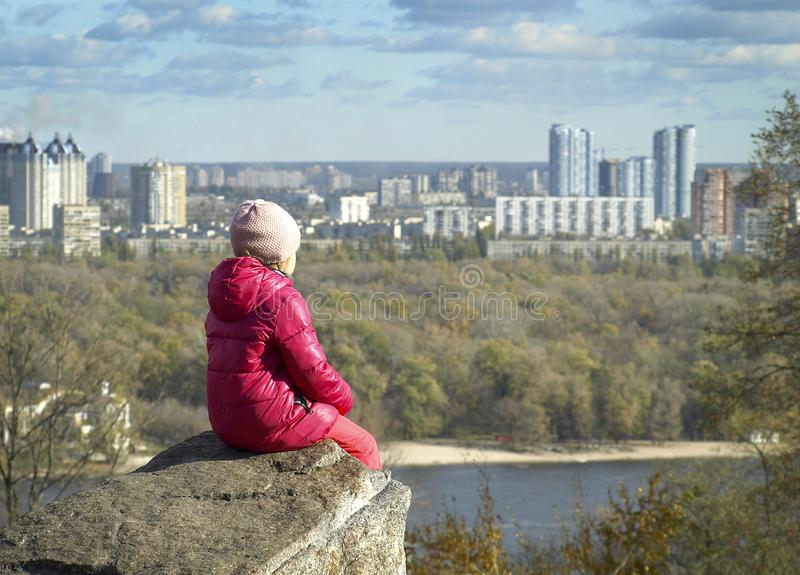 The girl sits on a rock and admires the urban landscape. royalty free stock photography