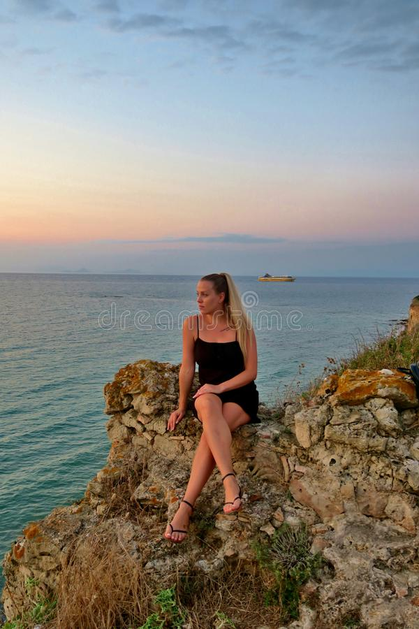 Girl sits on a rock and looks at a beautiful view of the sea and sunset royalty free stock photo